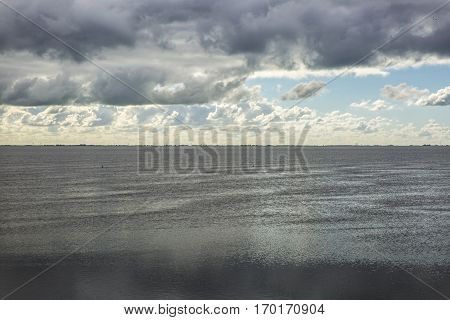 shoreline of Ameland Island with view over the wadden sea with clouds and tourmented sky reflecting in water at dawn