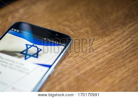 Smartphone On Wooden Background With 5G Network Sign 25 Per Cent Charge And Israel Flag On The Scree