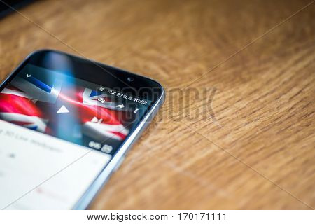 Smartphone On Wooden Background With 5G Network Sign 25 Per Cent Charge And Uk Flag On The Screen