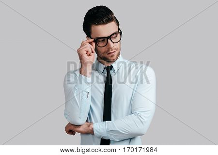 Thinking about solutions. Handsome young man in white shirt and necktie keeping arms crossed and adjusting his eyeglasses while standing against grey background