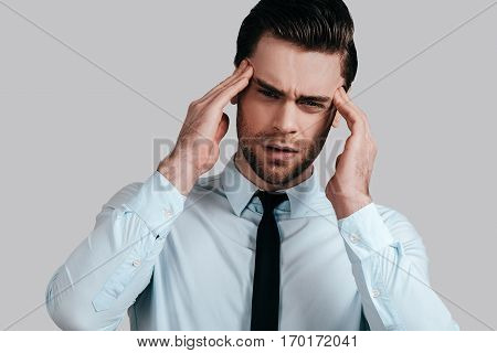 Feeling pain. Frustrated young man in formalwear touching his head with hands and making face while standing against grey background