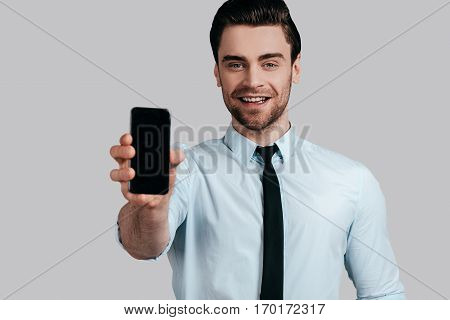 Copy space on his mobile phone. Good looking young man in white shirt and tie showing a smart phone and looking at camera while standing against grey background