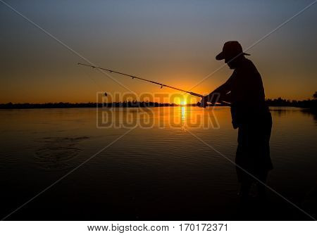 Young man fishing on a river from the boat at sunset silhouette