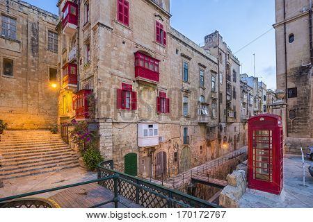 Valletta Malta - Red vintage british telephone box and footbridge and traditional red balconies in the ancient city of Valletta early in the morning
