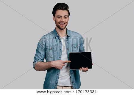 Copy space on his tablet. Handsome man in blue jeans shirt pointing copy space on his digital tablet and looking at camera while standing against grey background