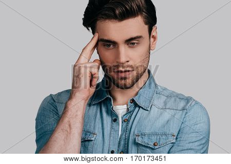 Fed up with everything. Frustrated young man in casual wear holding fingers on head and looking away while standing against grey background