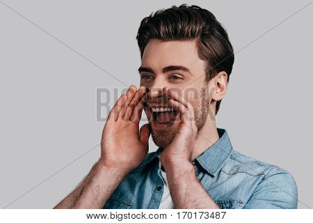 Everybody should hear it. Good looking young man in blue jeans shirt screaming and keeping hands over mouse while standing against grey background