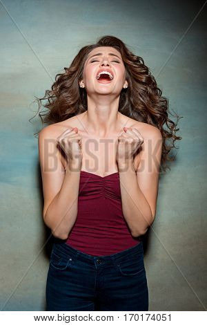 Portrait of young woman with shocked facial expression on gray studio background