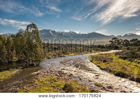 Shallow Stream In Corsica With Snow Capped Mountains In Distance