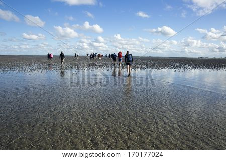 Maritime landscape with reflection of clouds in low tide water and group of people trekking Waddenzee Friesland The Netherlands poster