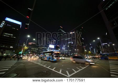 SEOUL - NOV, 3, 2015: People crossing road on crosswalk and cars move at night. Pedestrians in Seoul can now more safely get to streets of central areas
