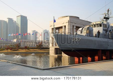 SEOUL - NOV 4, 2015: Military ship with cannonry in reservoir and highrise apartment buildings in military museum. In military museum was ceremony to mark 60th anniversary of armistice in Korea