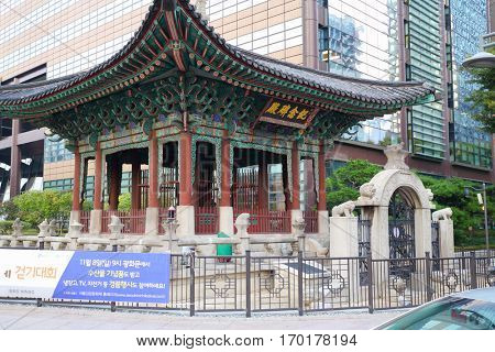 SEOUL - NOV 2, 2015: Painted old arbor with gate behind barrier near new building. Text translation - We invite you to attend 3rd Seoul Kimchi Cultural Festival