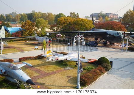 SEOUL - NOV 4, 2015: Freight big airplane near small and trees in military museum. South Korea started aerodynamic testing of next-generation fighter