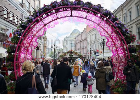 MOSCOW - APR 30, 2016: People walk on Arbat street with decorative arches at sunny day