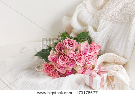 Female dress and jewellery with freah roses bouquet and gift box on chair