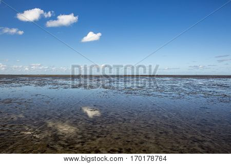 Maritime landscape with reflection of clouds in low tide water, Waddenzee Friesland The Netherlands