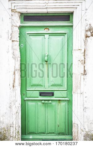 close up on a rustic old light green wooden door