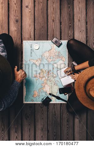 Couple Planning Vacation Sitting By The World Map.