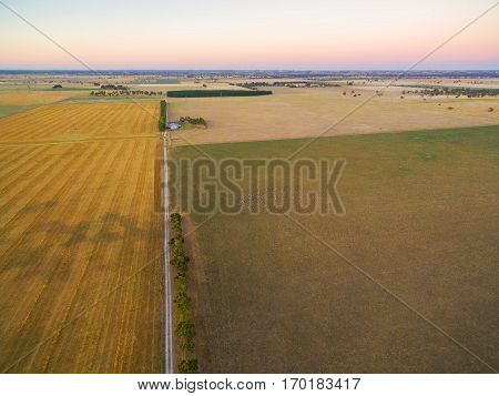 Harvested Agricultural Field And Pastures At Sunset In Rural Australia Aerial View.