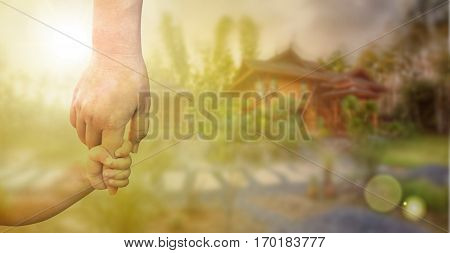 Children's hand and adult hand holding together over blur background of new wood house, dreaming about home, real estate and family concept