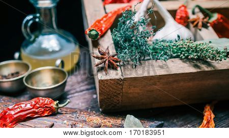 Bunces of thyme and tarragon, vinegar bottle and chili peppers amid other spices and herbs on cooking table. Close up view. Selective focus