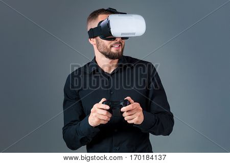 Emotional young man using a VR headset and experiencing virtual reality on grey background. A man dressed in a black shirt