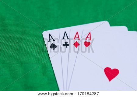 four aces on green desk close up