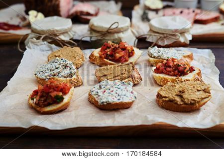 Close-up of mix of appetizers and toppings over crusty baguettes. Plate of assorted appetizers with chopped vegetables