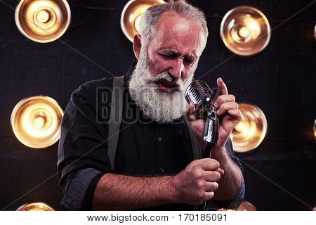 Close-up portrait of fashionable man in shirt and suspenders holding a microphone in isolated studio. Elegant man portrait. Model posing over spotlights background