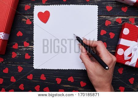 High angle of female hand writing on a greeting card for copy space. Gift boxes encircled with conceptual valentines symbols