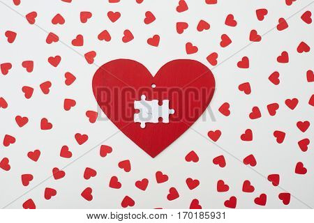 High angle of greeting card with two puzzle pieces. Heart surrounded with small. Red heart greeting card