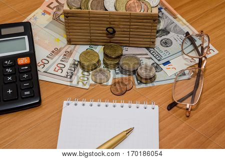 Open Treasure Chest With Coin. Us Dollar And Euro With Empty Notepad, Glasses And Calculator