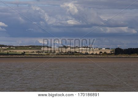 View from the Gironde estuary with the limestone cliff of the village of Meschers sur Gironde and its troglodytic houses and traditionnal typical wooden fisherman cabins Charente maritime France