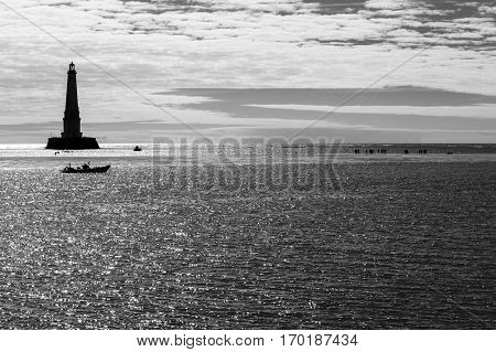 view over the sea with silhouette of the historical renaissance lighthouse of Cordouan at sunset Gironde estuary France