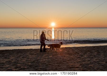 Silhouette of a man walking his dog on the beach by romantic winter sunset, Backlit silhouette of a man walking on a wooden pontoon over a lagoon at sunset, Nature reserve Casse de la Belle Henriette, l'Aiguillon sur Mer