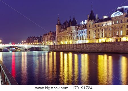Embankment of the Seine, the Ile de la Cite and Conciergerie at night, Paris, France