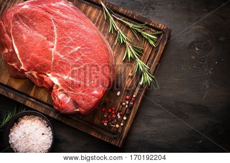 Raw meat. A large piece of beef chop on a cutting board with rosemary and spices.