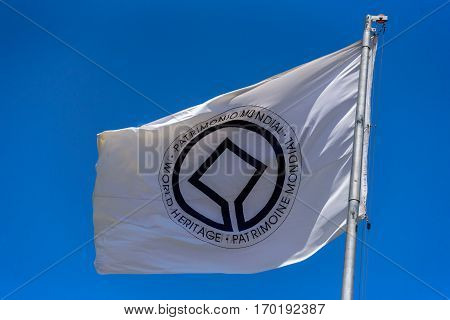 Flag of UNESCO World Heritage Committee waving in the wind at flagpole on the background of clear blue sky at sunny summer day
