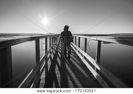 Black and white backlit silhouette of a man walking on a wooden pontoon over a lagoon at sunset, Nature reserve Casse de la Belle Henriette, l'Aiguillon sur Mer