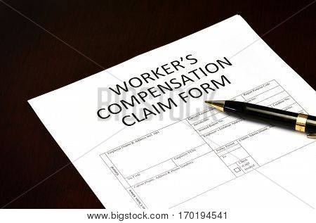 Worker's compensation claim form application with pen on desk