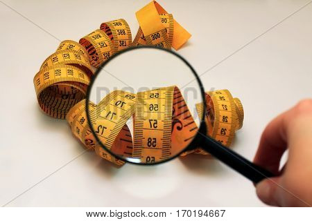 the magnifying glass aimed at measuring tape