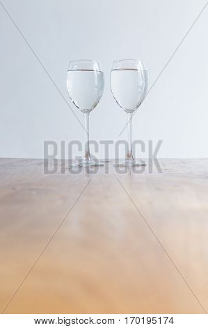 Two wine glasses filled with clear liquid on a wooden table