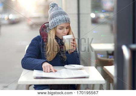 Woman With Coffee And Newspaper Outside