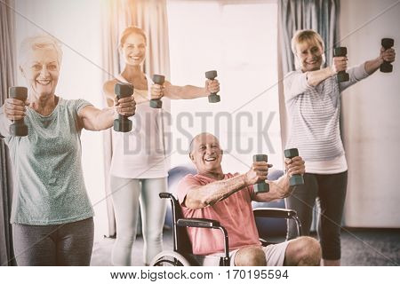 Portrait of seniors exercising with weights during sports class