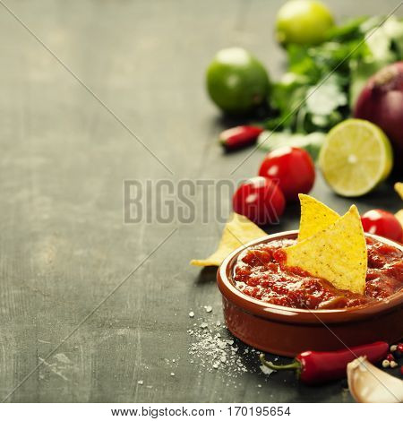 Fresh salsa dips with nachos chips and ingredients on old background. Space for text