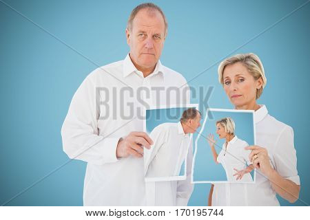 Angry older couple arguing with each other against blue background