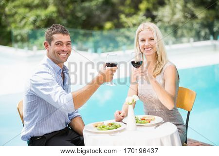 Portrait of smiling couple holding red wine while sitting at poolside