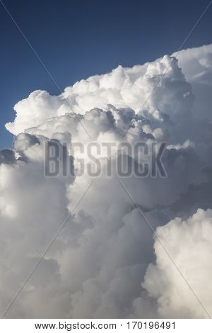 Close up on white fluffy storm clouds in front of blue sky