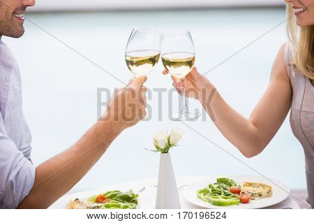 Cropped image of couple toasting white wine while sitting at poolside